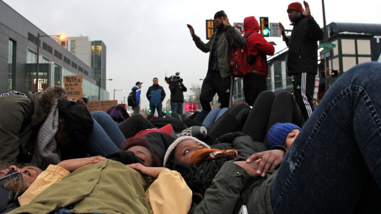 Temple students stage a die-in at Broad and Cecil B. Moore to protest police violence. (Emma Lee/WHYY)