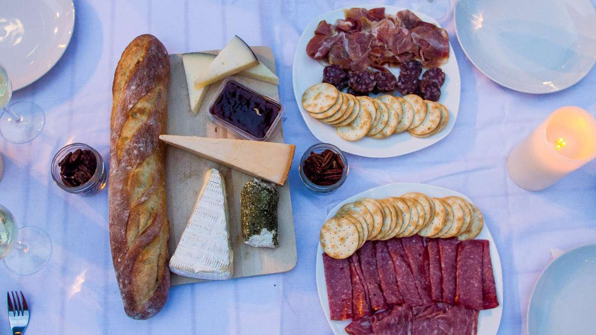 A baguette, cheeses and chacuterie sits on a table at Dîner en Blanc. (Brad Larrison/for NewsWorks)