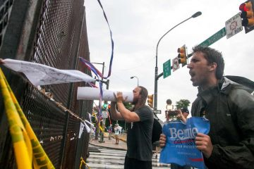 Bernie Sanders supporters yell through the security fence at the Democratic National Convention as delegates arrive for the final night of the event. (Brad Larrison for NewsWorks)