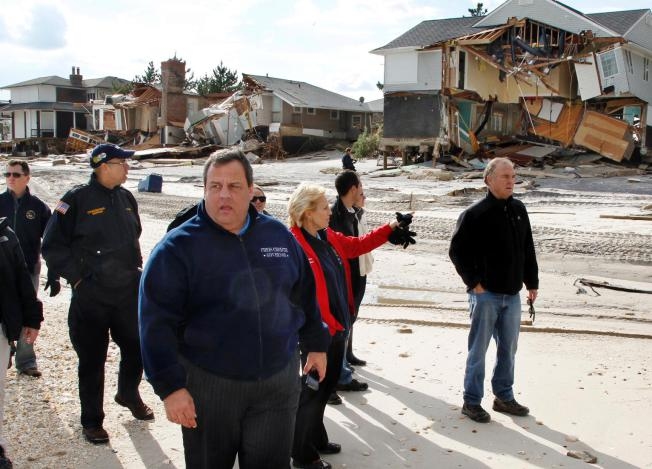 In this Nov. 2, 2012 file photograph, New Jersey Gov. Chris Christie, third from left, walks past damaged homes along the Atlantic Ocean in Mantoloking, N.J. after Superstorm Sandy hit the area on Oct. 29. (AP Photo/Mel Evans, Pool, File)
