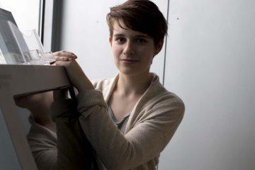 Anna Gibbons, a public health major at Drexel University,stands by the mental health screening kiosk. (Karen Shakerdge/ NewsWorks)