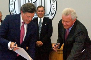 Larry Kaiser, president and CEO of Temple University Health System, left, and Jeffrey Immelt, GE chairman and CEO, sign papers finalizing the agreement.(Jessica McDonald/WHYY)