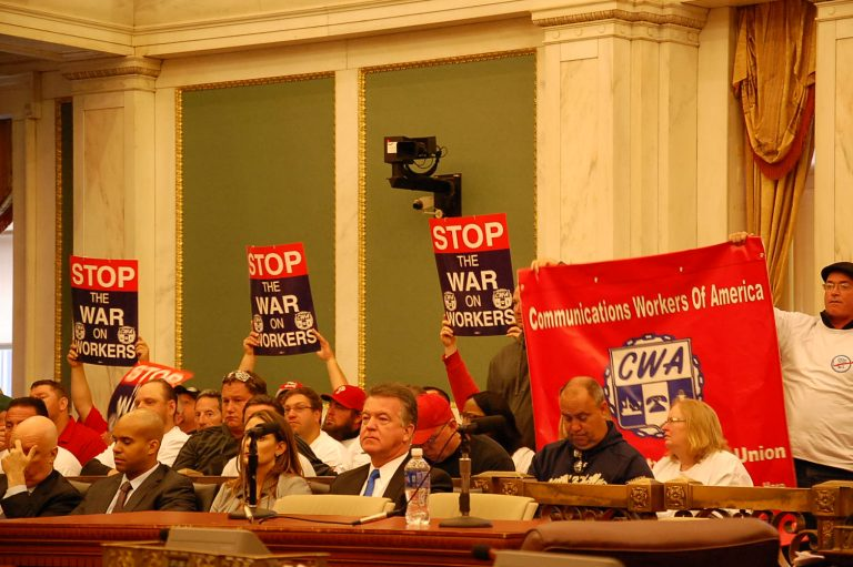 Verizon workers make their feelings known during Friday's City Council hearing. (Tom MacDonald/WHYY)