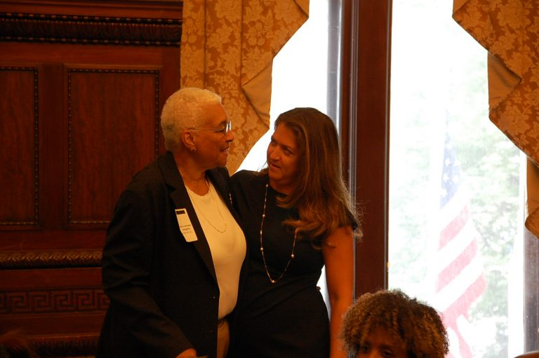 Incoming DHS Commissioner Cynthia Figueroa (right)greets Estelle Richman