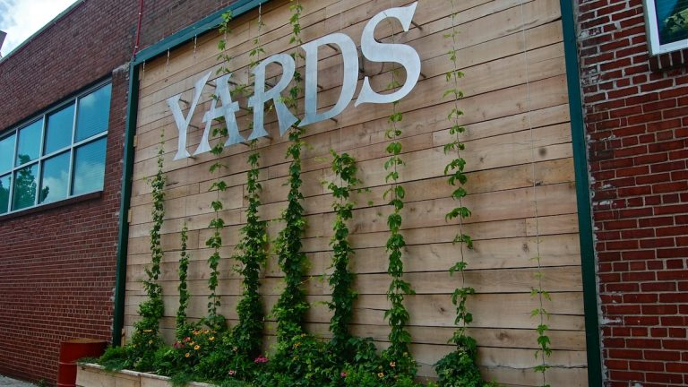 The wall, which dons a brand new Yards Brewery sign, is made of black locust, a native tree that grows along the banks of the Schuylkill and is currently growing three kinds of hops. (Emily Brooks/for NewsWorks)