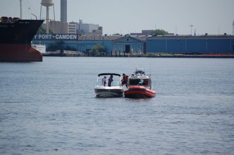 A Coast Guard member boards a boat in a drill for stopping BUI (Boating Under Influence). (Tom MacDonald/WHYY)