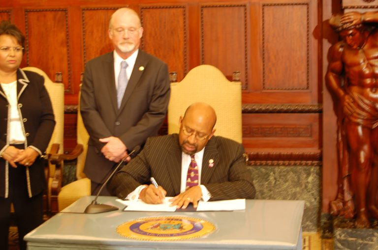 Philadelphia Mayor Michael Nutter signs sick leave bill as Councilman Greenlee stands by (Tom MacDonald/WHYY)