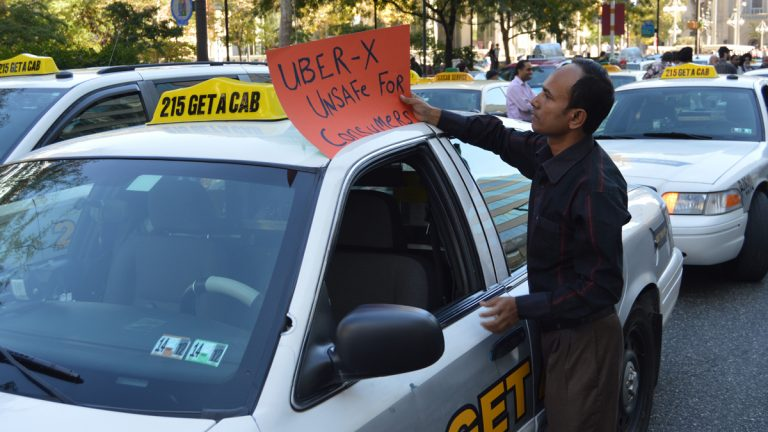 A cab driver places a sign protesting UberX