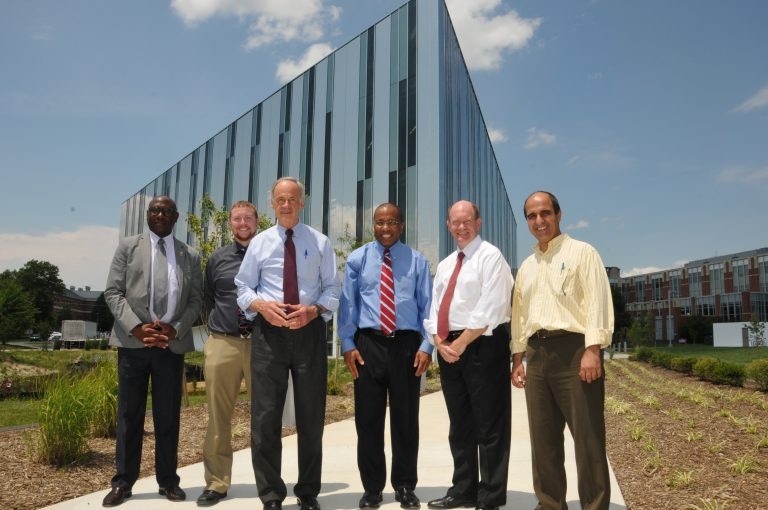 Senators Tom Carper (third from left) and Chris Coons (second from right) pose with Delaware State president Harry Williams (center) outside the university's new optics facility. (Photo courtesy of Delaware State University)
