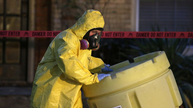 A hazmat worker moves a barrel while finishing up cleaning outside the apartment of a hospital worker who tested positive for ebola in Dallas.  (AP Photo/LM Otero)