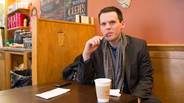 Gregory Conley takes a drag of an electronic cigarette in an Old City cafe.  Philadelphia lawmakers have since banned smoking e-cigarettes indoors and in public spaces similar to tobacco products.  (Lindsay Lazarski/WHYY)