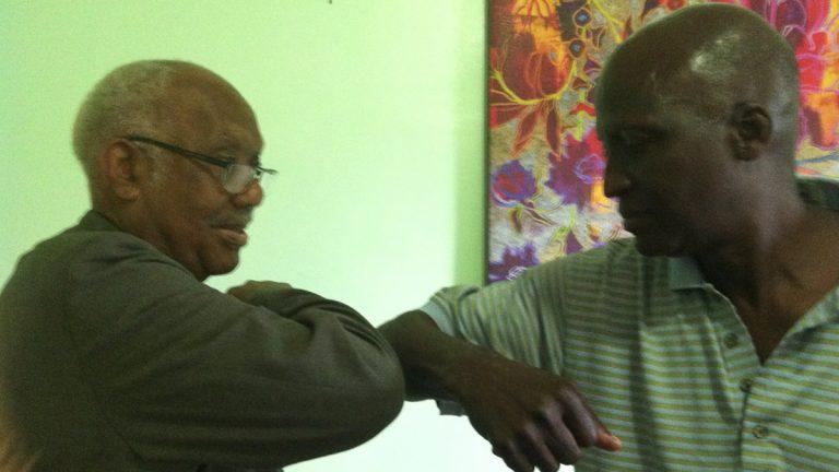 Francis Horton and Voffee Jabateh demonstrate the 'Ebola handshake' meant to minimize contact. (Elana Gordon/WHYY)