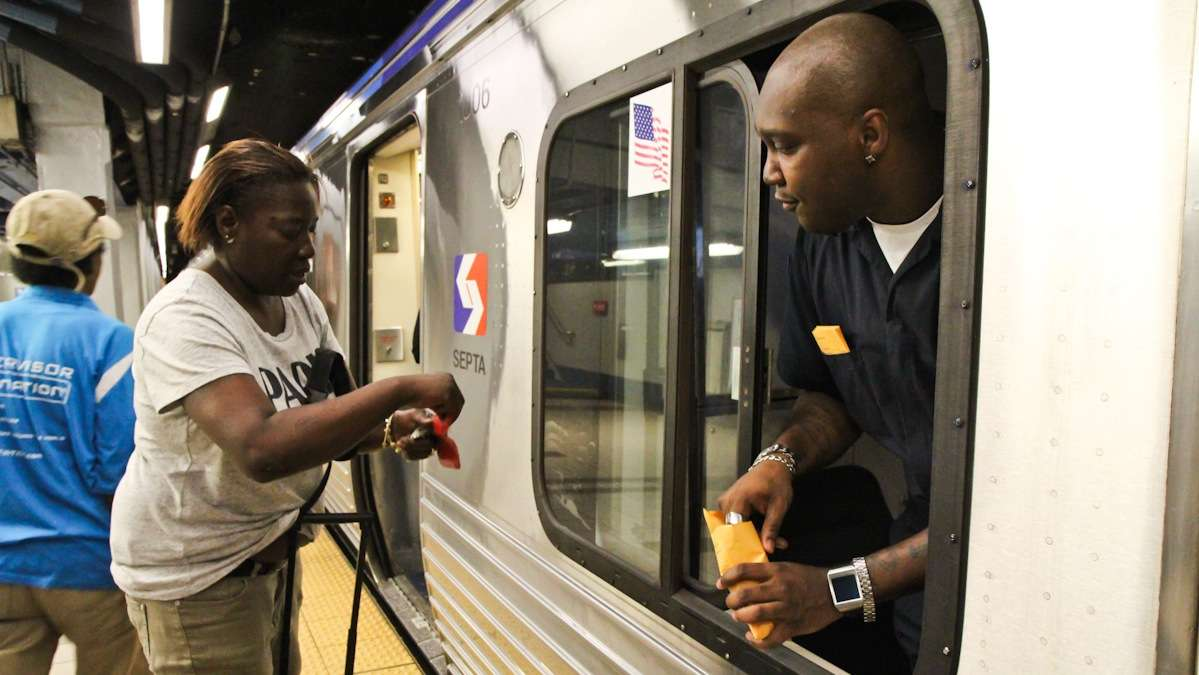 Train operator Maurice Bey collects fares at the front of the train for Nite Owl service (Kimberly Paynter/WHYY)