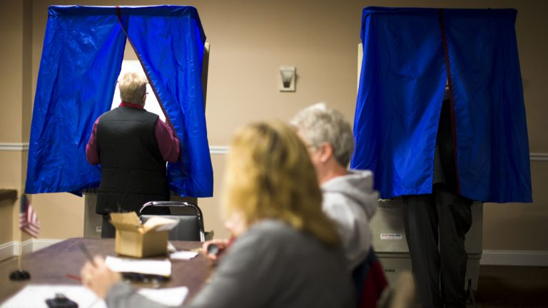 A voter steps into voting booth at the Oregon New Years Association in Philadelphia. An analysis of Department of State data shows turnout in Pennsylvania's struggling communities in 2010 was down nearly 20 percent from 1994. (AP Photo/Matt Rourke)