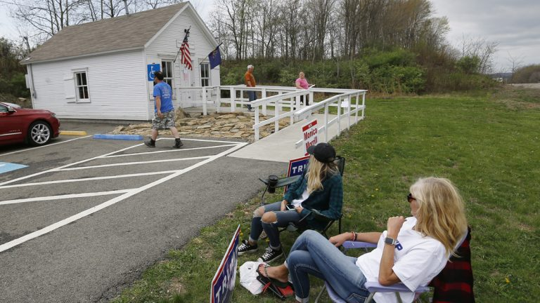 A few campaign workers sit outside the small polling location called the Simpson Voting House in New Alexandria, Pa. (AP Photo/Keith Srakocic)