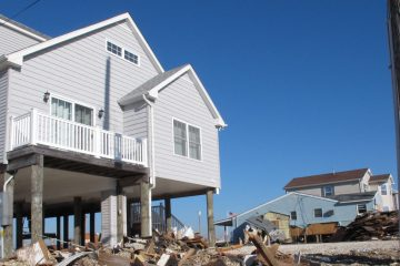The home on the left, in Tuckerton, N.J., emerged from Superstorm Sandy intact because it was elevated. (AP Photo/Wayne Parry)