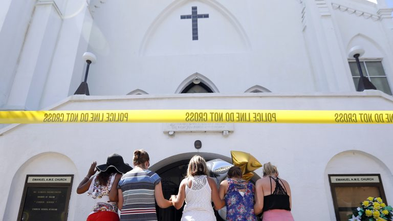A group of women are shown praying together on the sidewalk in front of the Emanuel AME Church in Charleston