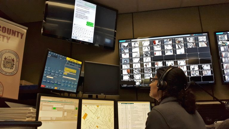 A call center operator monitors screens at Montgomery County Emergency Services Center, which now include text messages to 911. (Laura Benshoff/WHYY)