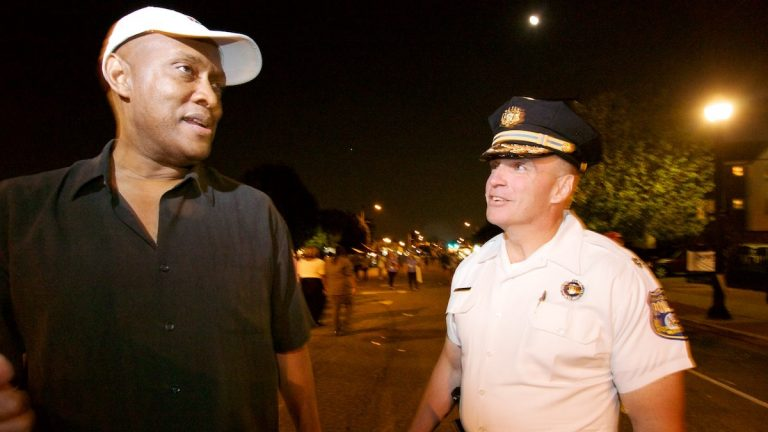 State Rep. Dwight Evans and Police Inspector James Kelly walk along Ogontz Avenue at the West Oak Lane Night Market in June. (Bas Slabbers/for NewsWorks, file)