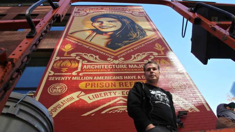 Shepard Fairey prepares to put the finising touches on his mural at the Friends Center at 15th and Race streets. (Emma Lee/WHYY)