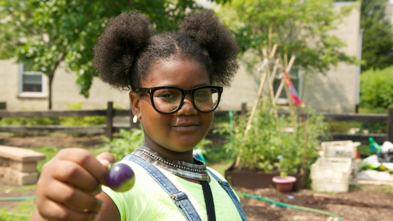 Tahtanique Smith holds up an almost-ripe Cherokee purple tomato grown on the farm. (Nathaniel Hamilton/For Newsworks)
