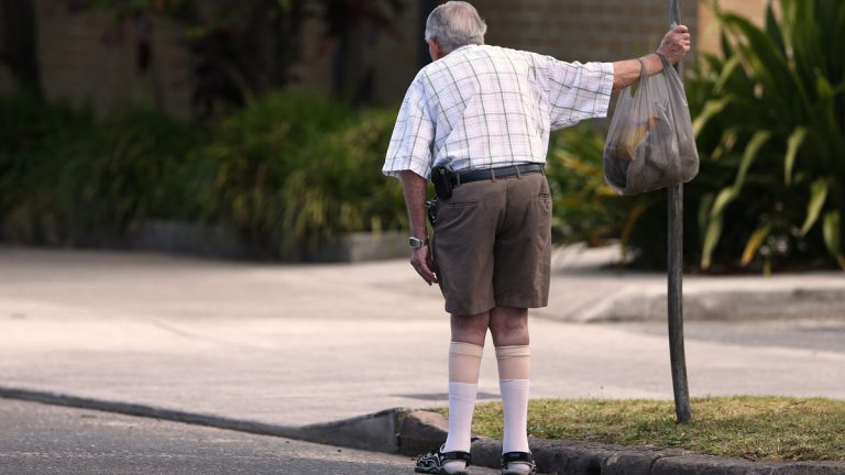 In this Oct. 11, 2013 photo, an elderly man holds onto a signpost on the side of a road in Sydney. About a third of people over 65 fall every year, according to the World Health Organization. (AP Photo/Rick Rycroft, File)