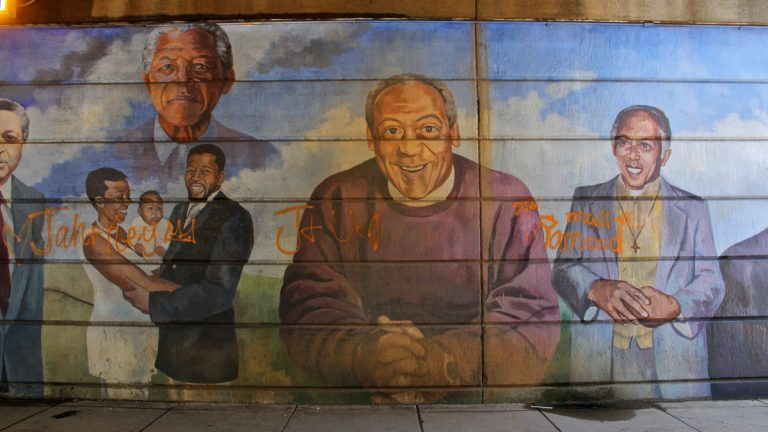 Philadelphia's Mural Arts Program has stepped up its plans to remove the damaged Father's Day mural on Broad Street in North Philadelphia. Bill Cosby figures prominently in the work.(Emma Lee/WHYY)