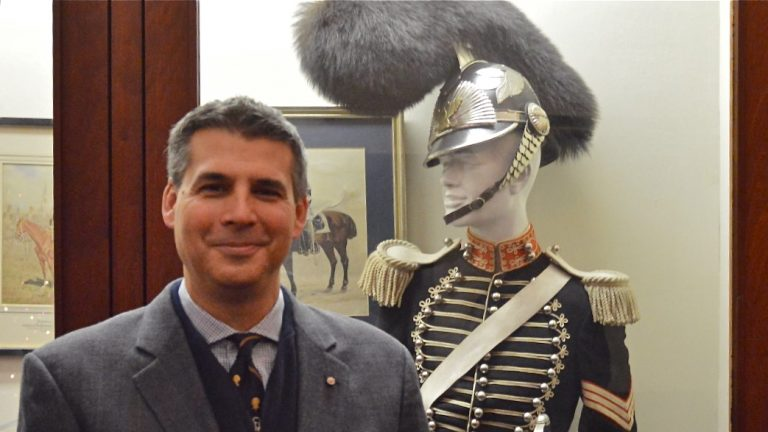 Andre Stephano of the First Troop stands next to the ceremonial uniform designed in 1825 that members of his group will wear in Donald Trump's  inaugural parade Jan. 20. (Tom MacDonald/WHYY)