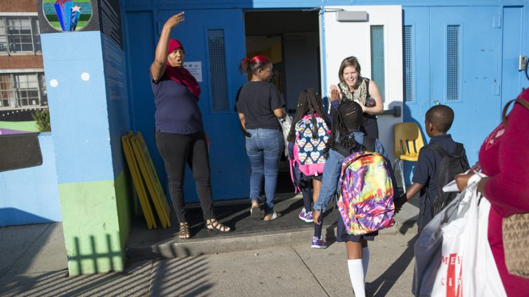 Administrators and teachers give students high-fives and help them navigate their first day of school at Mastery Charter School John Wister Elementary in Philadelphia