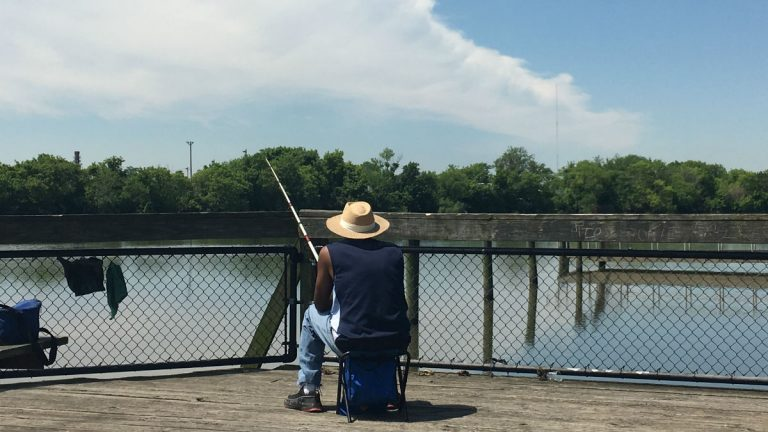 An angler fishes off a dock along the Christina River in Wilmington. (Mark Eichmann/WHYY)