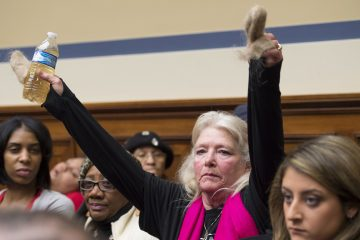 Glaydes Williamson of Flint, Mich., holds up a bottle of Flint water and handfuls of hair on during testimony at the House Oversight and Government Reform Committee hearing on Feb. 3 to examine the ongoing situation. (AP Photo/Molly Riley)