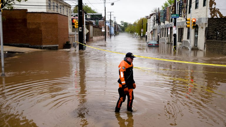 Marine unit police officer Robert Jonah walks through flood waters from the Schuylkill River on Main Street in the Manayunk neighborhood of Philadelphia on May 1