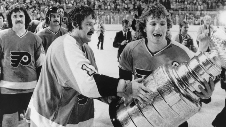 Philadelphia Flyers Bernie Parent, left, and Bobby Clarke, carry the Stanley Cup off the ice in  Buffalo on May 28, 1975, after winning over the Buffalo Sabres. (AP Photo, file)