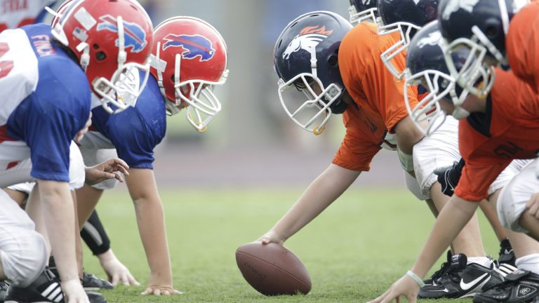 Players line up in three-point stances during a 6th grade youth football game in Richardson