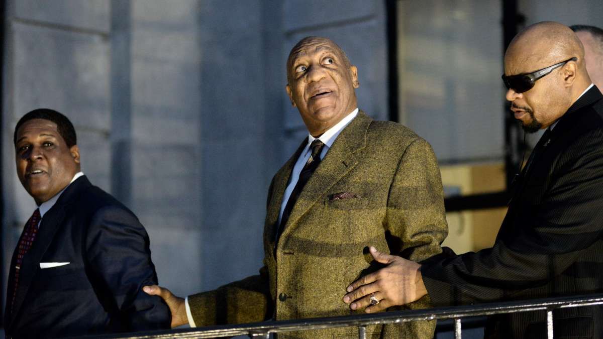 The spotlights of rolling cameras hit Bill Cosby's face as he looks up at the media helicopters above him seconds after he leaves Montgomery County Courthouse