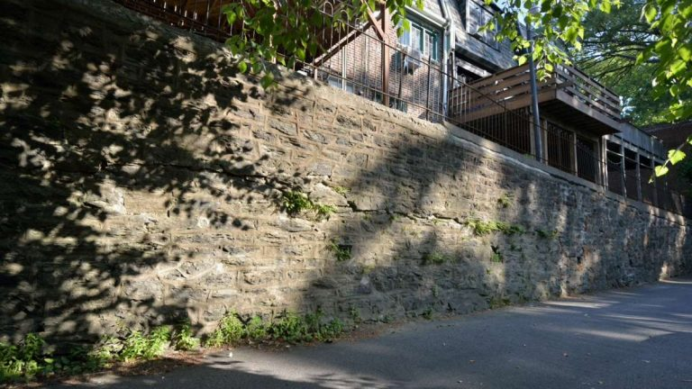 The 550-foot stone-masonry retaining wall that separates the rear alley of houses along West Penn Street from the common driveway of homes along Midvale Avenue is leaning, cracked and unsafe. (Bas Slabbers/for NewsWorks, file)
