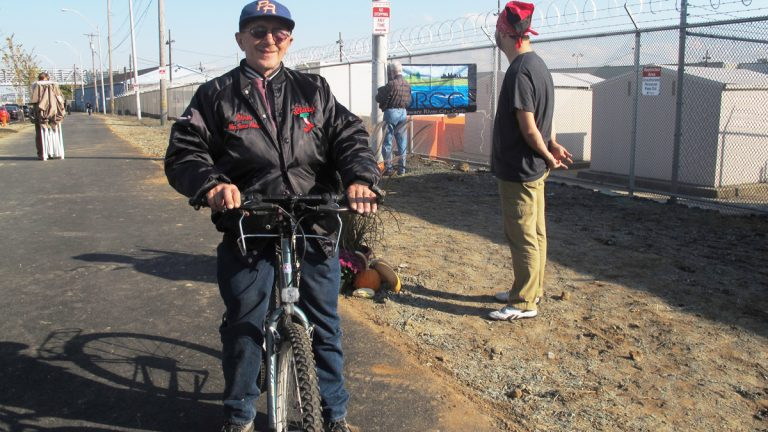 Port Richmond resident Frank Stypulkowski rides his bike on the new trail along the Delaware River waterfront. The Port Richmond Trail is a key link in the Circuit, a network of trails in New Jersey and Pennsylvania (Katie Colaneri/WHYY).