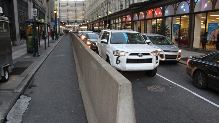 Traffic on Eighth Street is restricted by a concrete barrier in preparation for the reconstruction of The Gallery mall. (Emma Lee/WHYY)