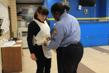WHYY Urban Life Correspondent Elizabeth Fiedler straps on a bulletproof vest for her ride-along with police in South Philadelphia. (Kimberly Paynter/WHYY)