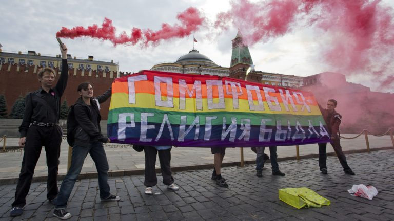 Gay rights activists hold a banner reading