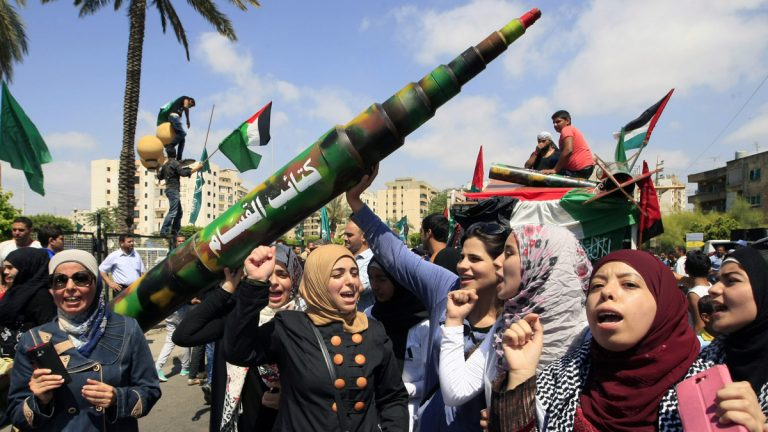Palestinians and Lebanese women carry a fake missile to protest against the Israeli offensive in Gaza, as they take part in a rally organized by Palestinian group Hamas and Lebanon's Islamic Group in the southern port city of Sidon, Lebanon, Friday, July 11, 2014. (AP Photo/Mohammed Zaatari)