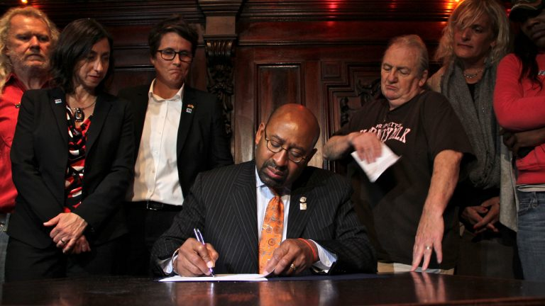 Mayor Michael Nutter signs a law banning gender signs on single-user bathrooms. The act was applauded by members of the city's trans gender communities. (Emma Lee/WHYY)