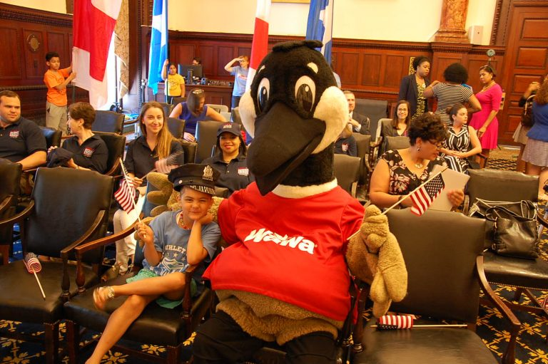 Wawa's mascot and a friend listen to the announcement of Welcome America activities.(Tom MacDonald/WHYY)