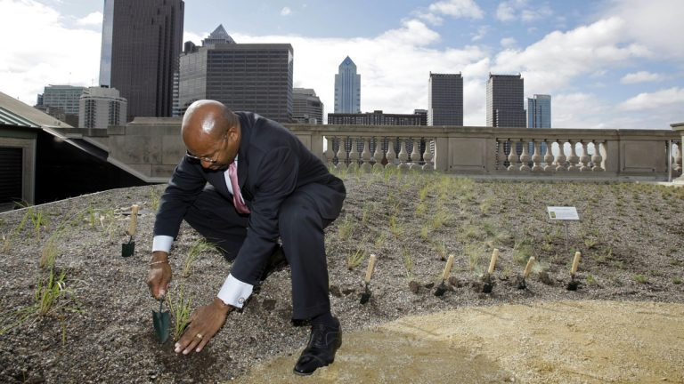 Mayor Michael Nutter places a plant into the roof of the Free Library of Philadelphia during a ceremony in 2008. (AP Photo/Matt Rourke)