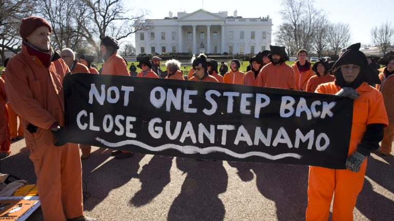 Protesters wearing orange jumpsuits