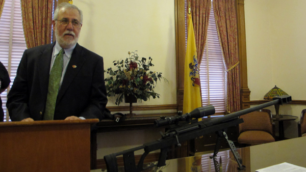 Brian Miller, with the gun violence prevention group Heeding God's Call, displays a disabled 50-caliber rifle at a Statehouse news conference Friday. (Phil Gregory/for NewsWorks)