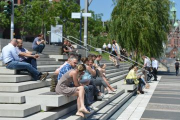 People gather for lunch on steps overlooking a waterway in HafenCity. (Wulf Rohwedder/for Keystone Crossroads)