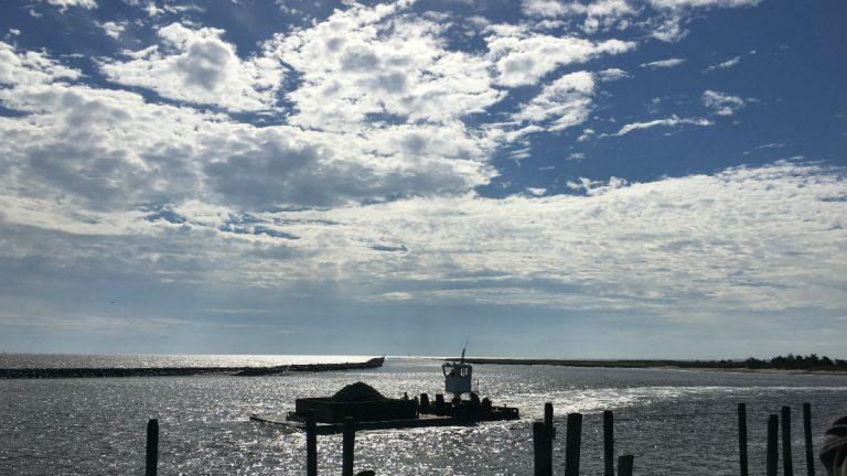 A tugboat pushes a barge full of rocks through Mispillion Harbor. (Mark Eichmann/WHYY)