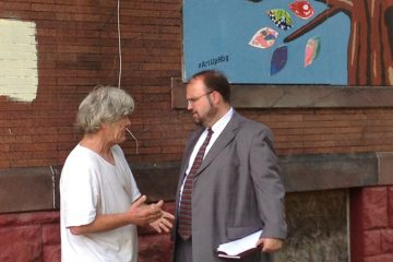 Harrisburg Mayor Eric Papenfuse talks with a city resident at an event to highlight an initiative that will board up blighted buildings with artwork.  (Emily Previti/WITF)