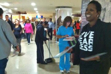 Valerie Myers, a representative from Independence Blue Cross, hands out information about health insurance during the morning commute at Philadelphia's Suburban Station.  (Elana Gordon/WHYY)